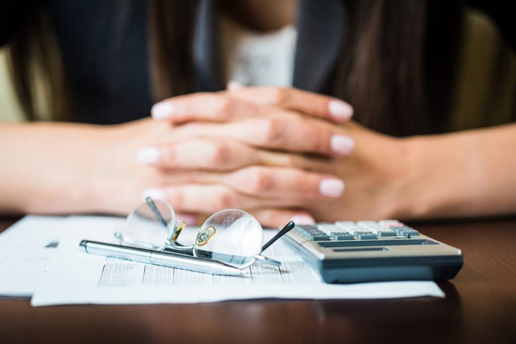 Close up of businesswomans hands with pen, glasses, and calculator doing some financial calculations