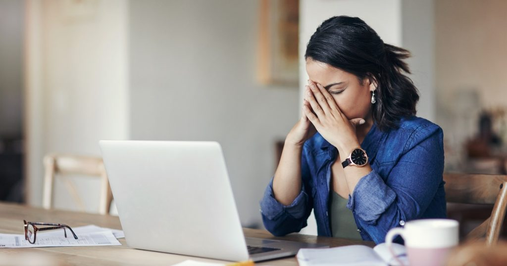 Shot of a young woman looking stressed while using a laptop at home
