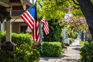 Leafy suburban neighborhood with American flags hung from houses