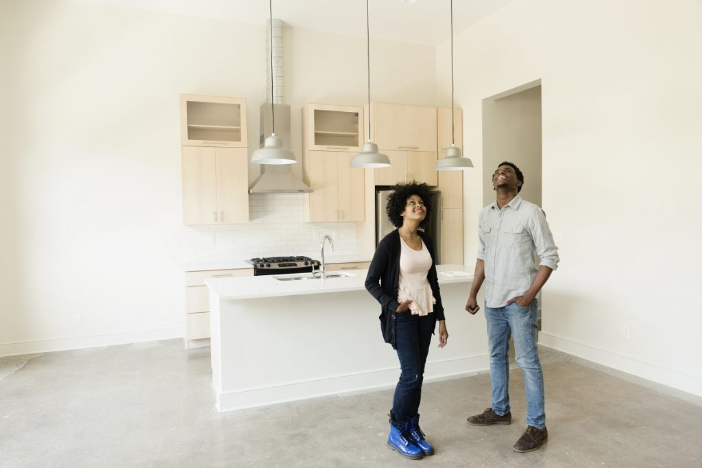 Young couple standing in kitchen in new house