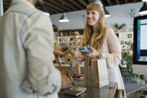 Smiling customer paying shop owner with credit card at counter