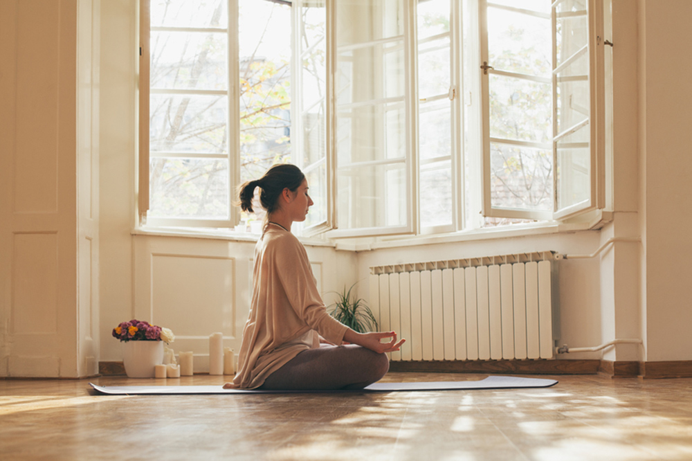 woman meditating in new apartment