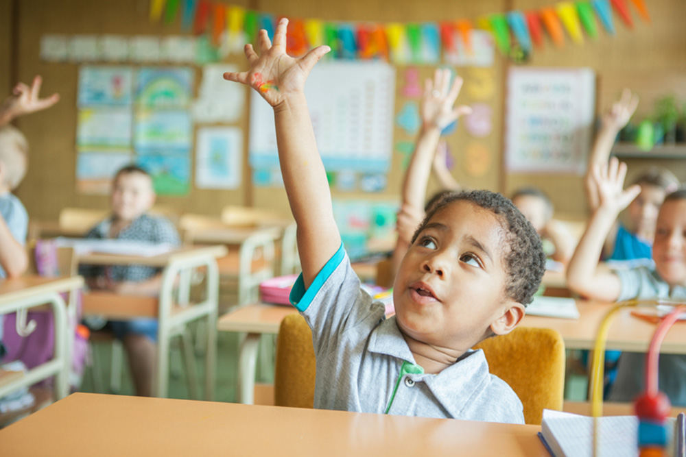 kid raising hand in class