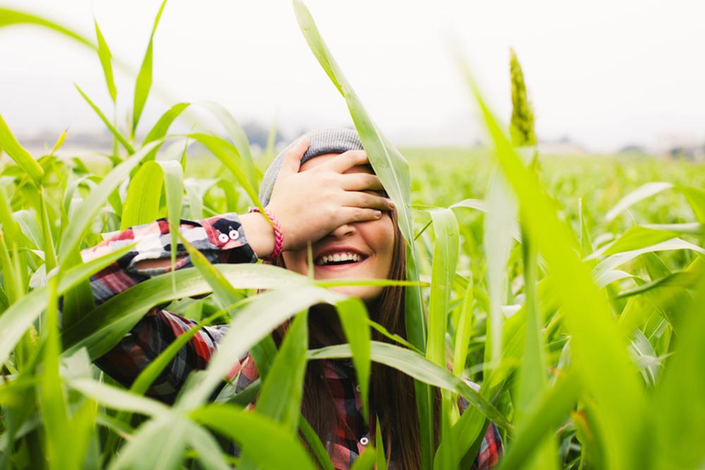 woman in field hiding face