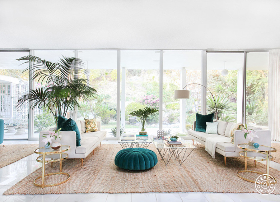 Light filled white living room with teal tufted ottoman.