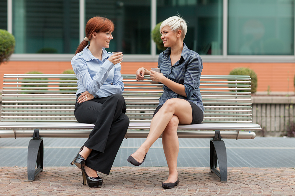 two business women talking on bench