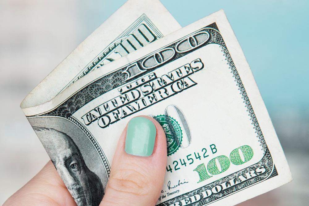 hand holding one hundred dollar bill