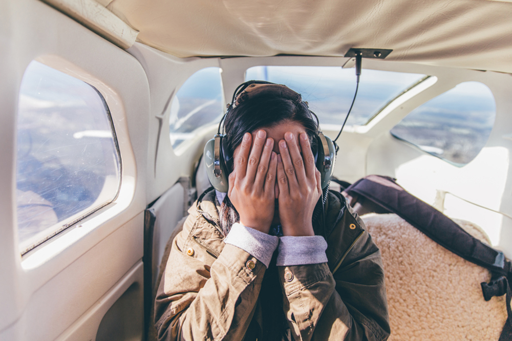 girl closing her eyes on an airplane