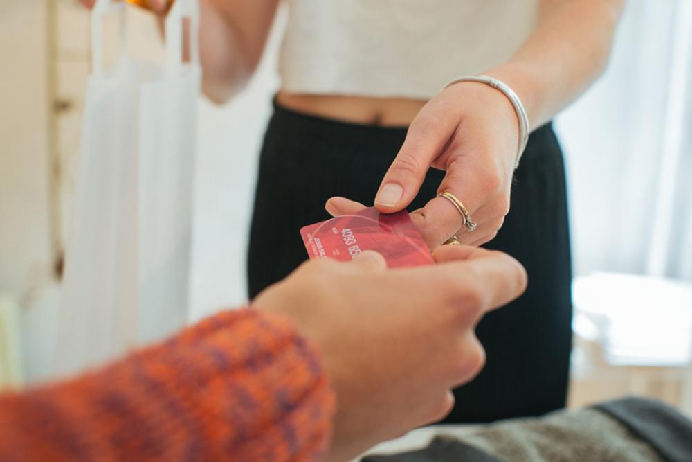 woman handing over credit card