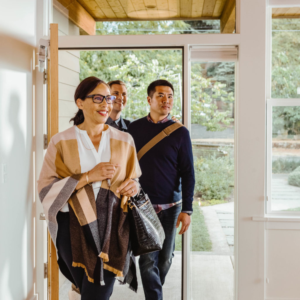 Female real estate agent walks into the front entry of a house with her clients, a couple, behind her