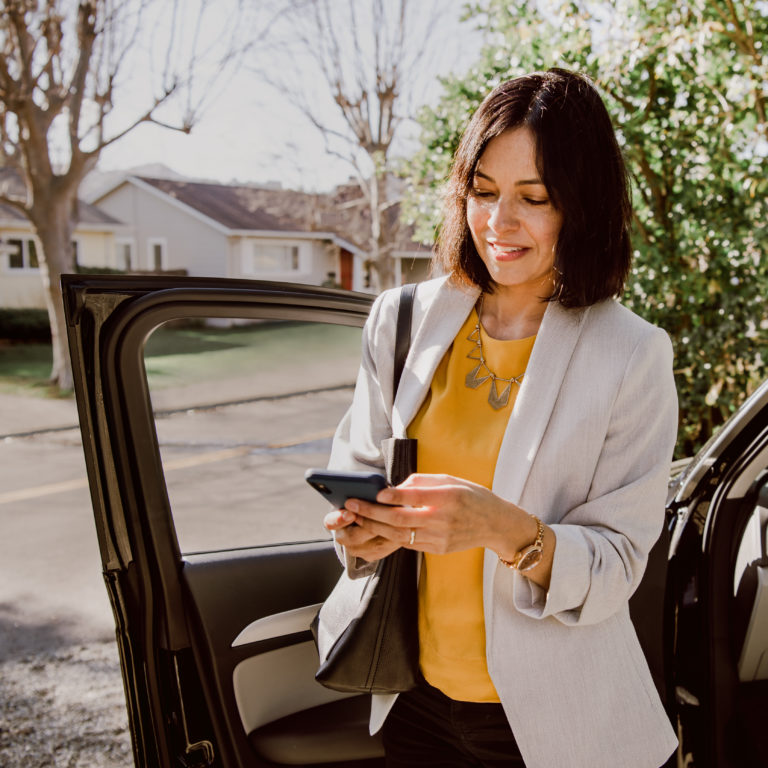 Real estate agent checking her mobile phone after she gets out of a car
