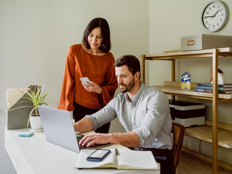 Two real estate agents in an office looking at information on a laptop screen