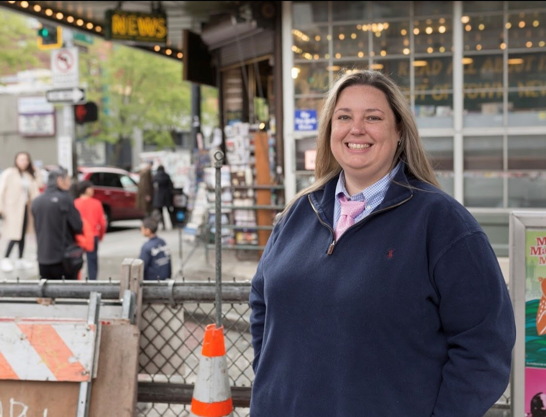 Snapshot of Zillow employee Brenna Penrod. She's wearing a navy blue zip-up sweatshirt and is standing in front of a news stand surrounded by construction cones at Seattle's Pike Place Market.