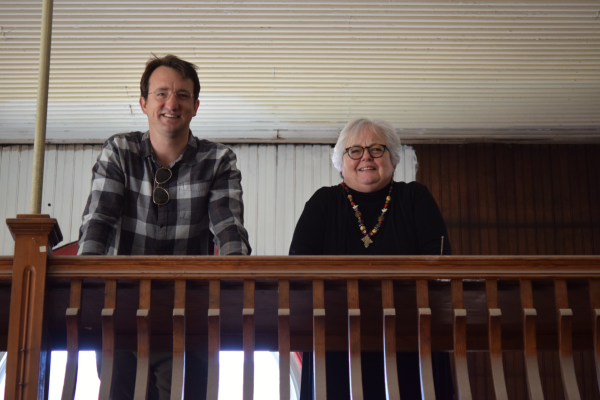 Man and woman stand on interior balcony of historic building