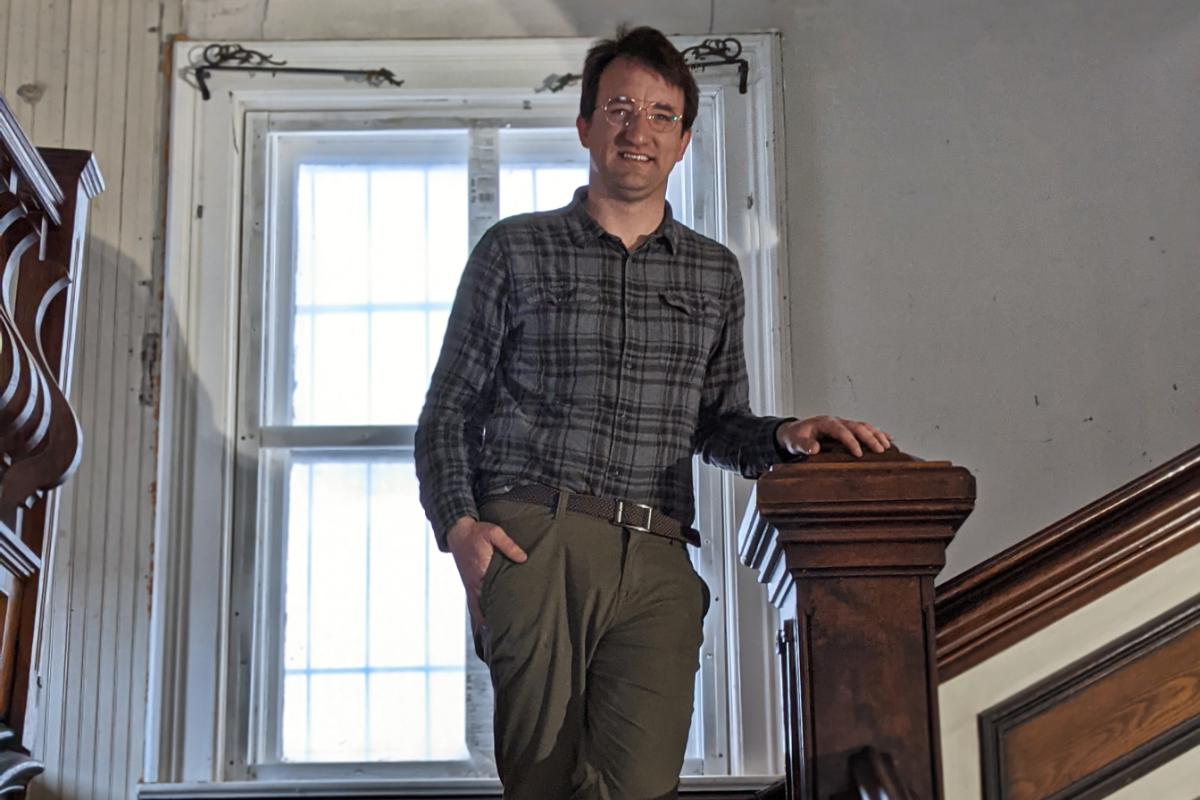 Man standing on stair landing in old building