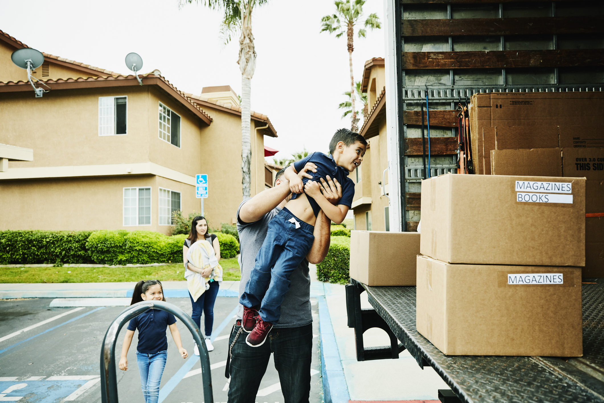 ather lifting smiling son into back of moving truck