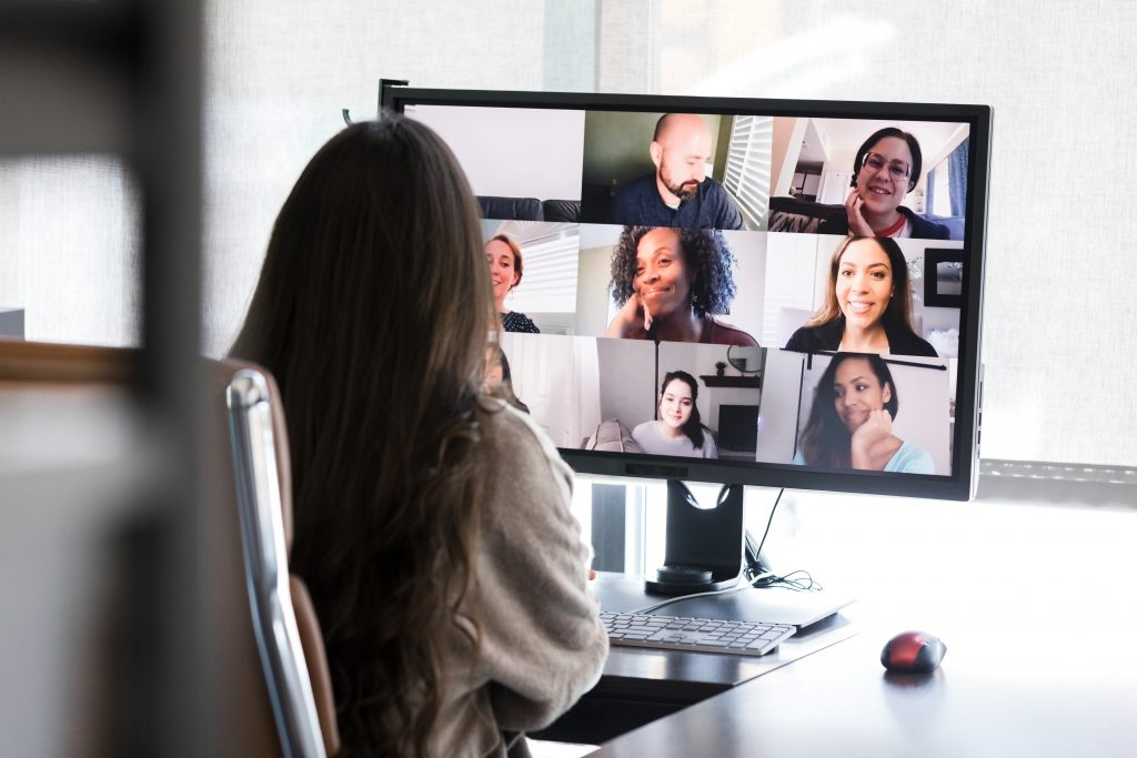woman looking at computer screen which has a series of video conference screens on it