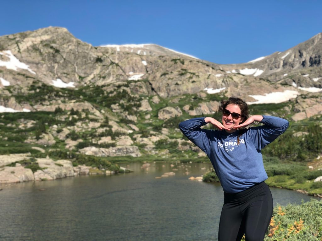 Woman standing in front of lake with mountain range in the background. She holds her hands below her chin to make the shape of a smile.