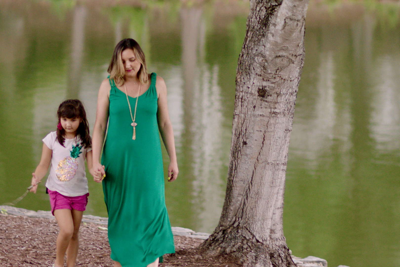 Woman holding child's hand as they walk alongside a lake
