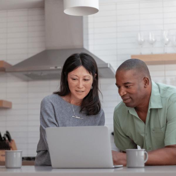 man and woman looking at laptop computer screen
