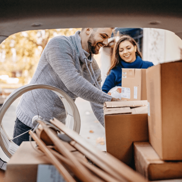 man and woman loading boxes into a car