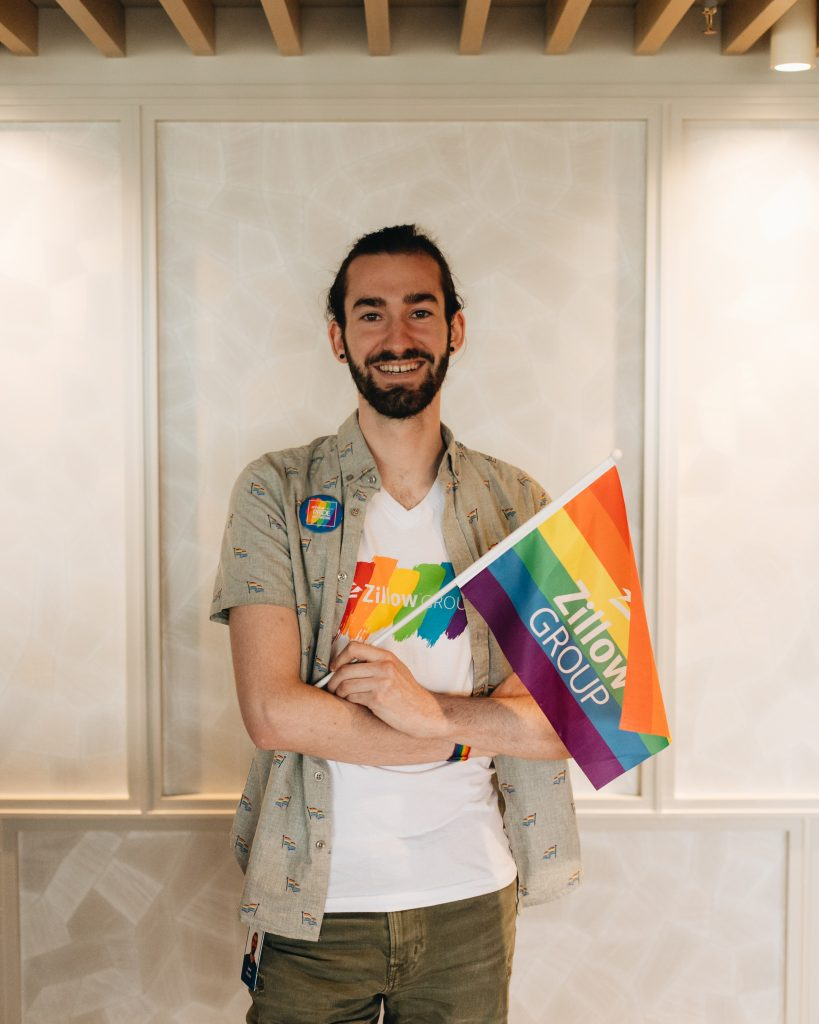 Portrait of software developer Jake Piccini, wearing a Zillow Pride network t-shirt and holding a small Pride flag