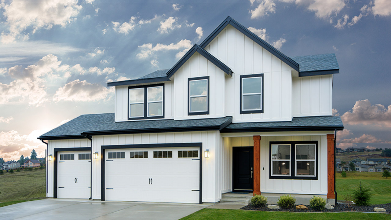 White 2-story house with 3 car garage surrounded by grass