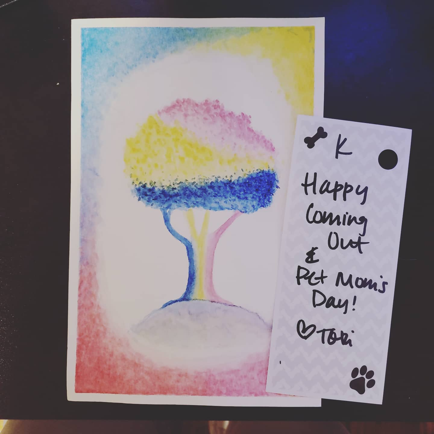 A card with an illustration of a person with short curly rainbow-colored hair that reads Happy Coming Out
