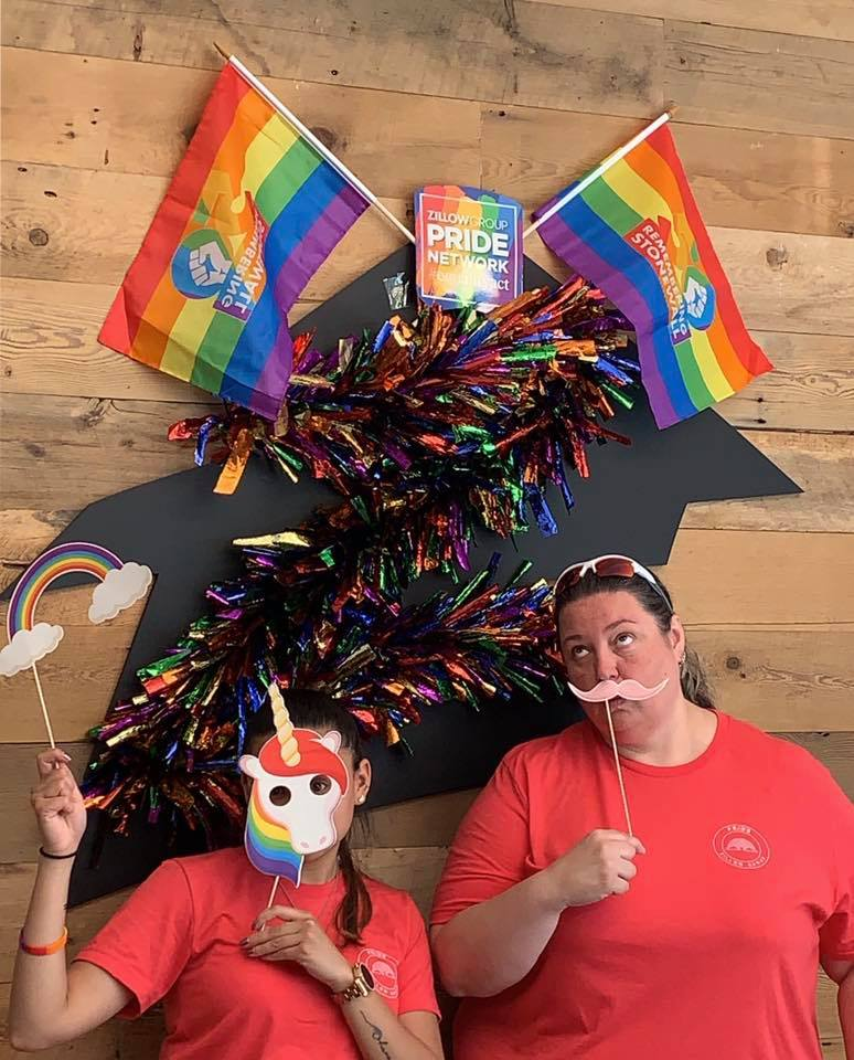 Snapshot of two people wearing masks with PRIDE flags hung on the wall behind them.