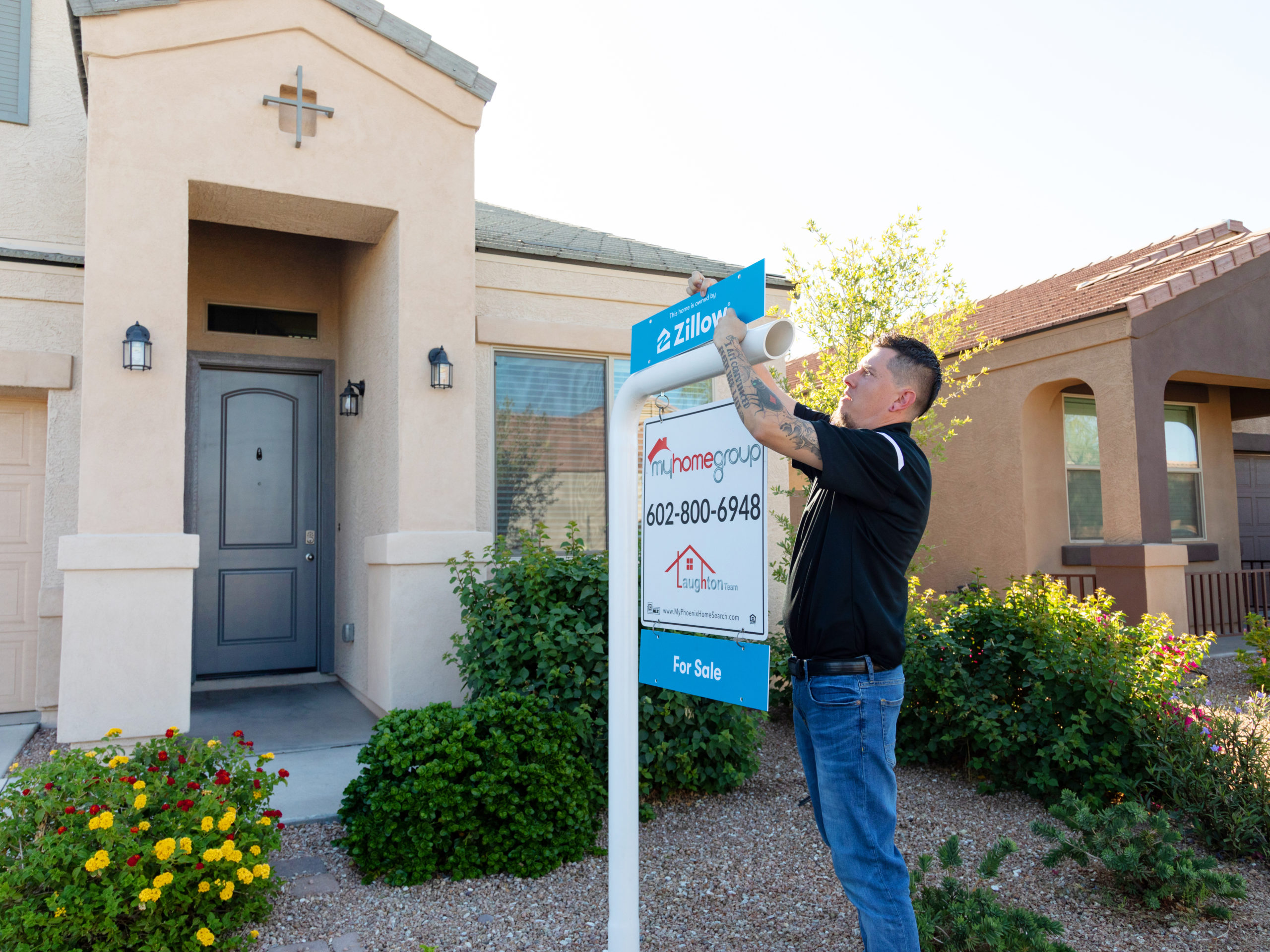 Worker installing Zillow Offers for sale sign in front of single family home