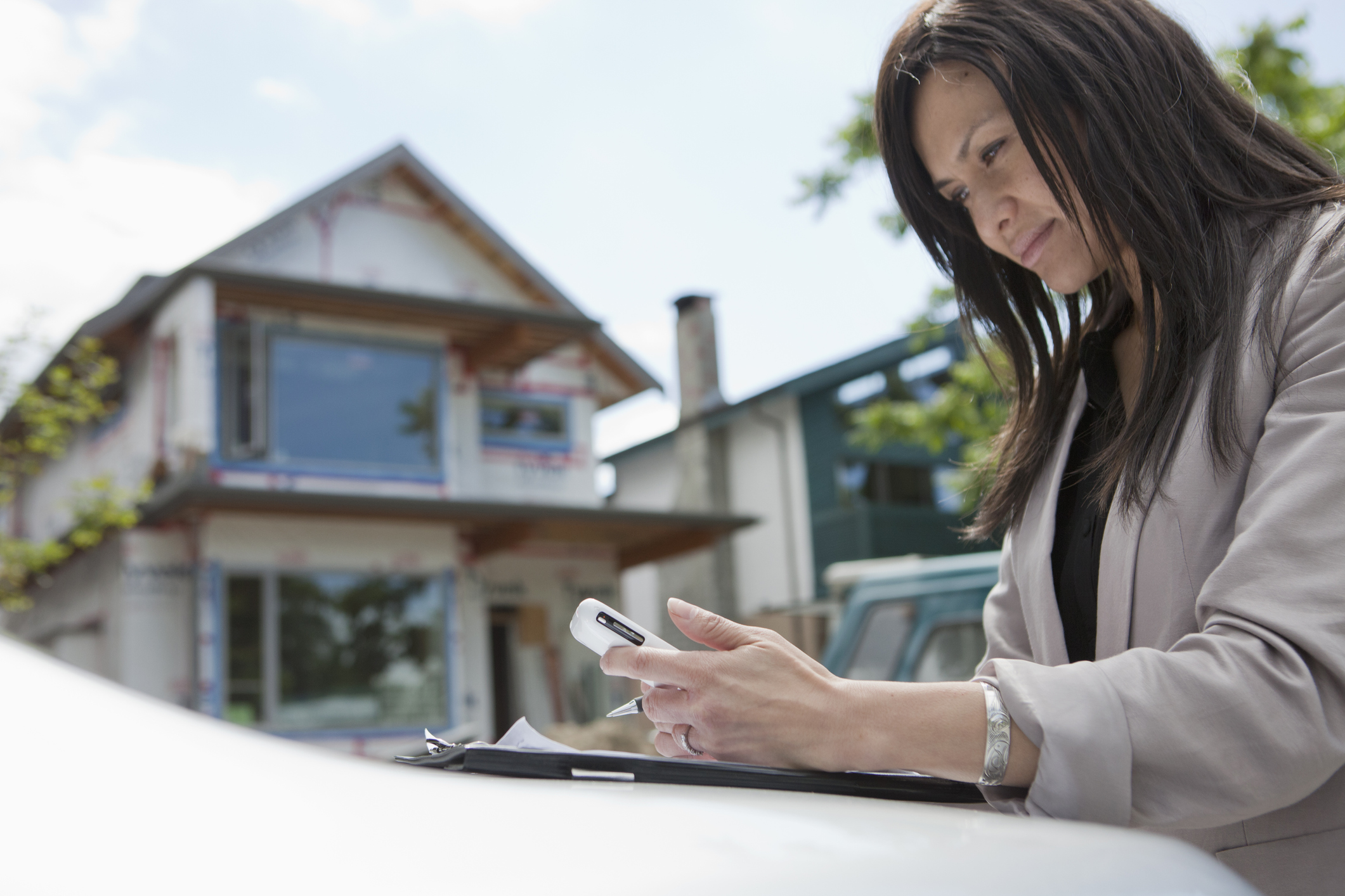 real estate agent texting on phone outside of home