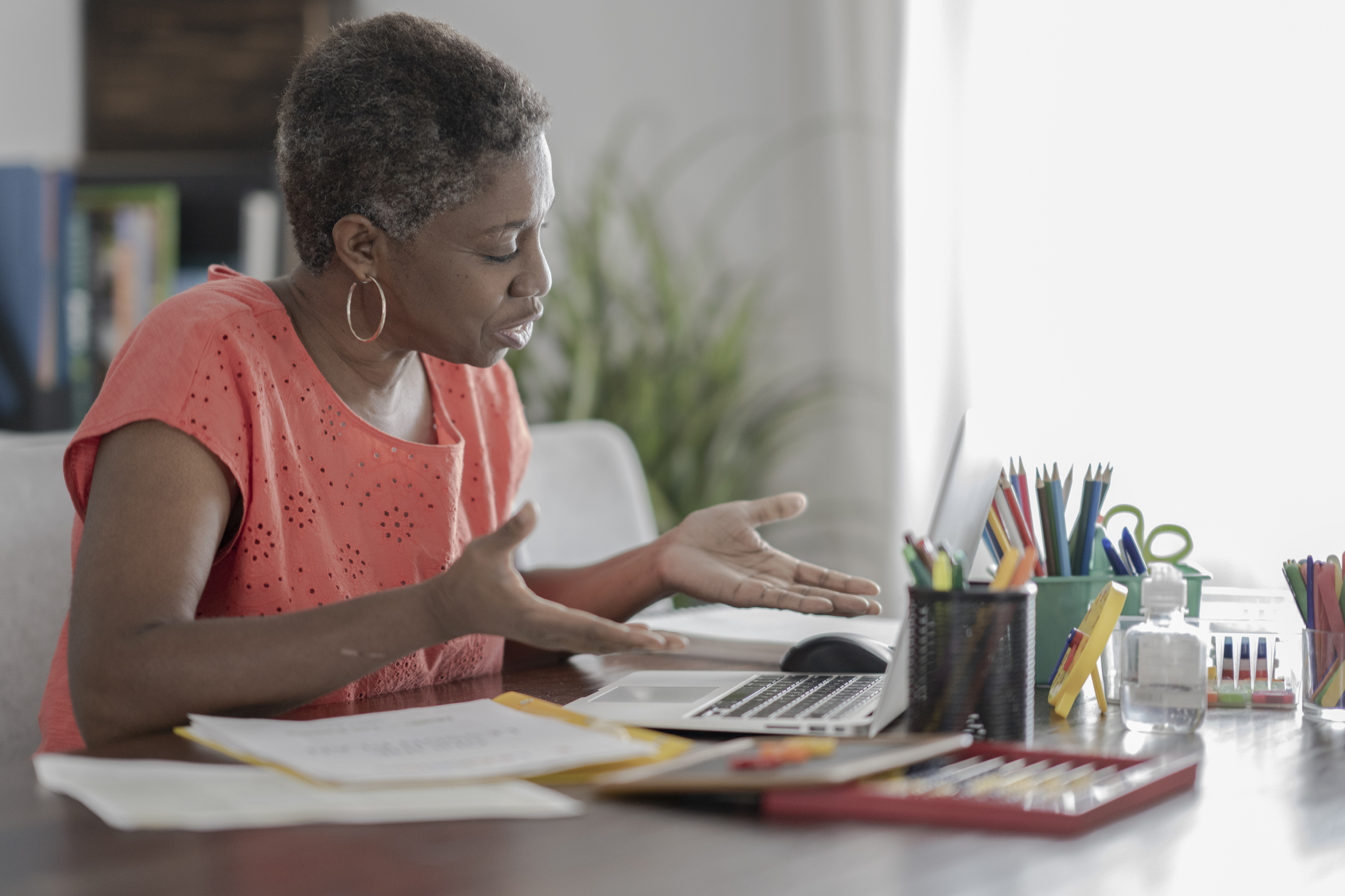 Black woman at desk looking into computer screen