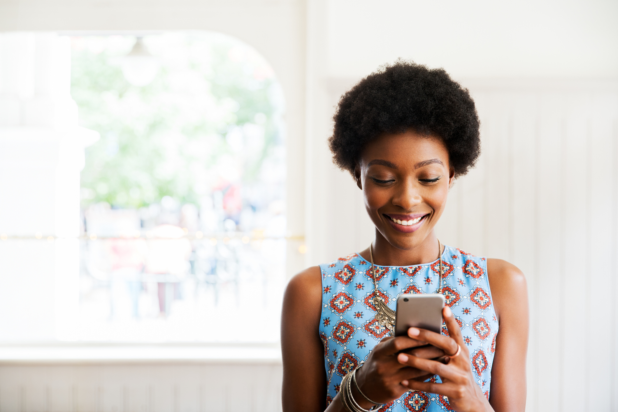 woman smiling looking at floor plan on her smart phone
