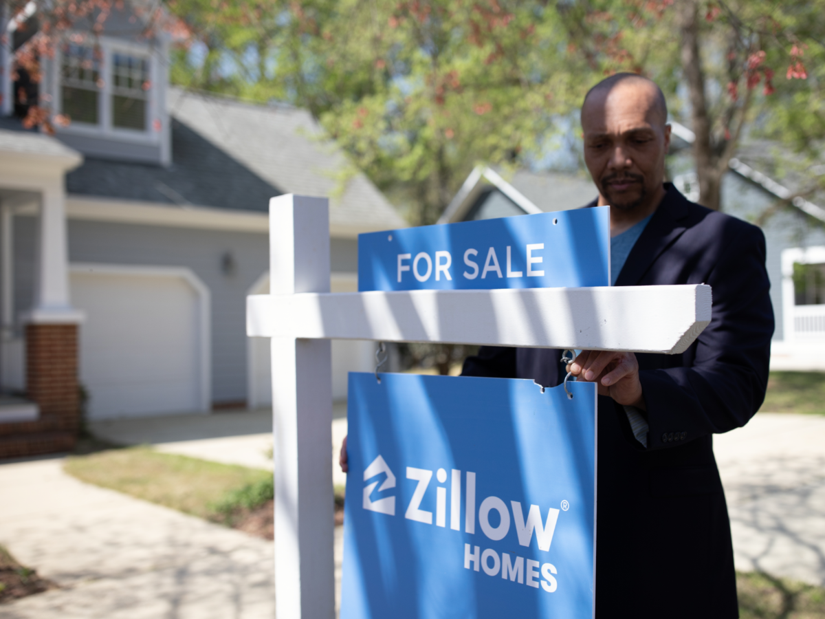 agent hanging up zillow homes for sale sign in front of a house