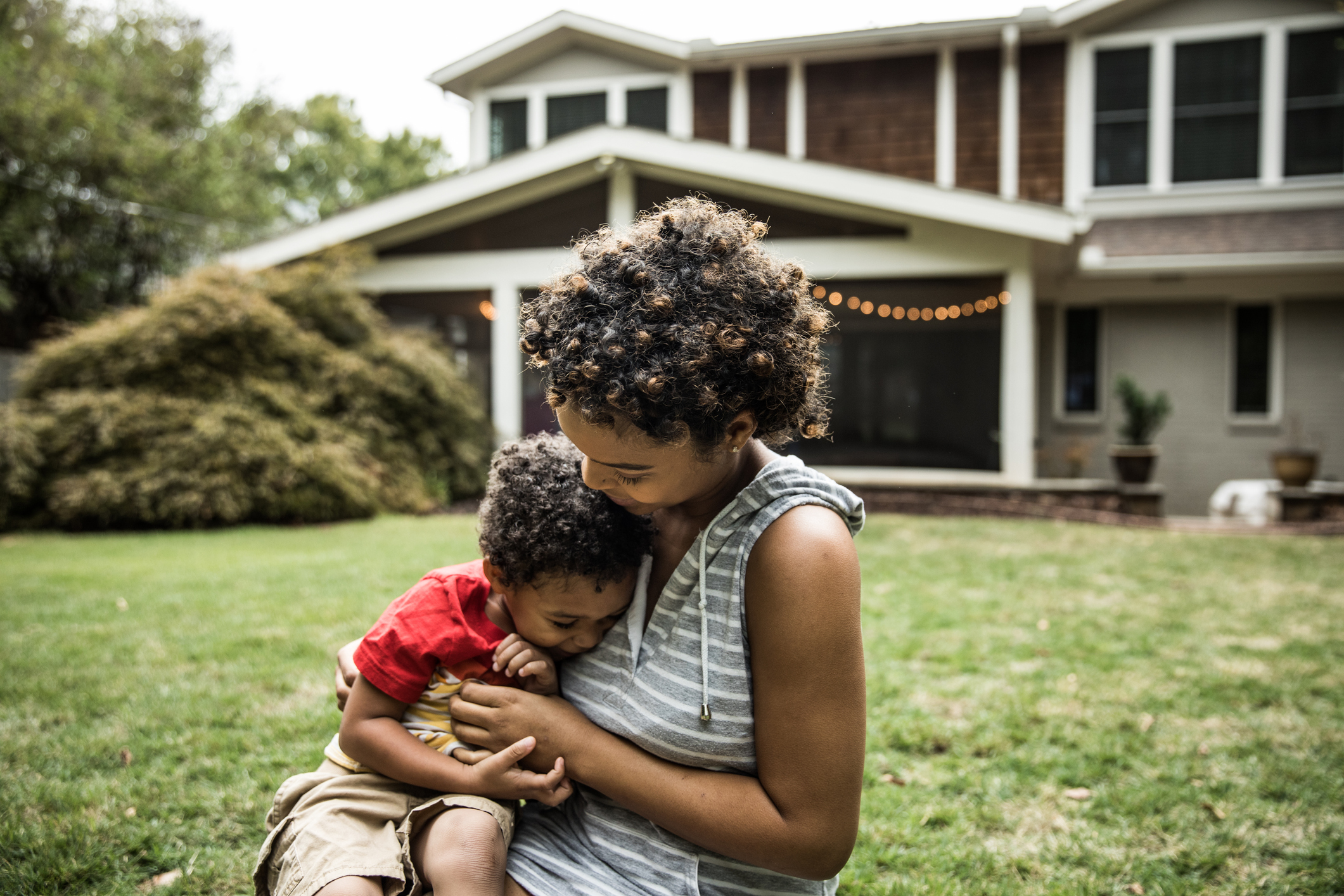 mother, toddler sit in grass in front of 2-story house