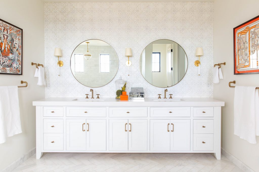 a bathroom with a white antique-looking bureau with sinks mounted in it and circle-shaped mirrors on the wall